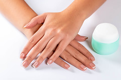 Beautiful woman hands with light manicure on nails and a jar of cream