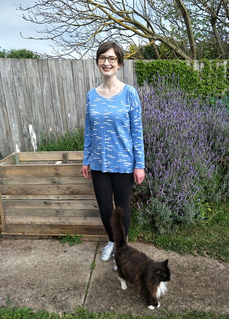 A woman stands in front of a garden fence. She wears a blue long sleeve tee with white cloud-like print, black leggings and silver runners. She is smiling. A cat poses in front of her.