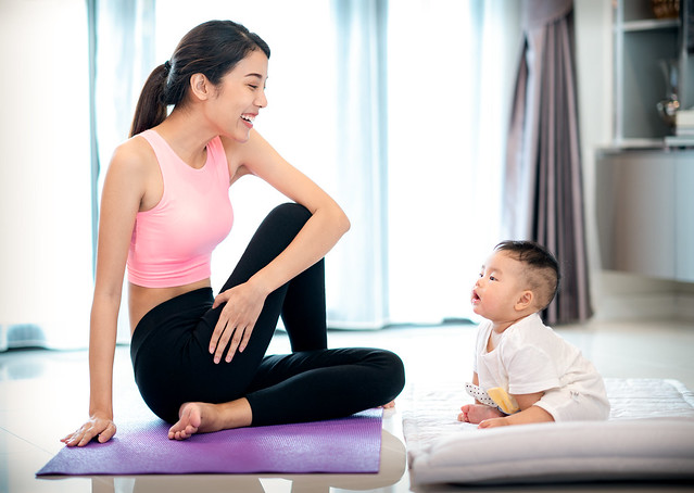Mother in yoga action and baby in home