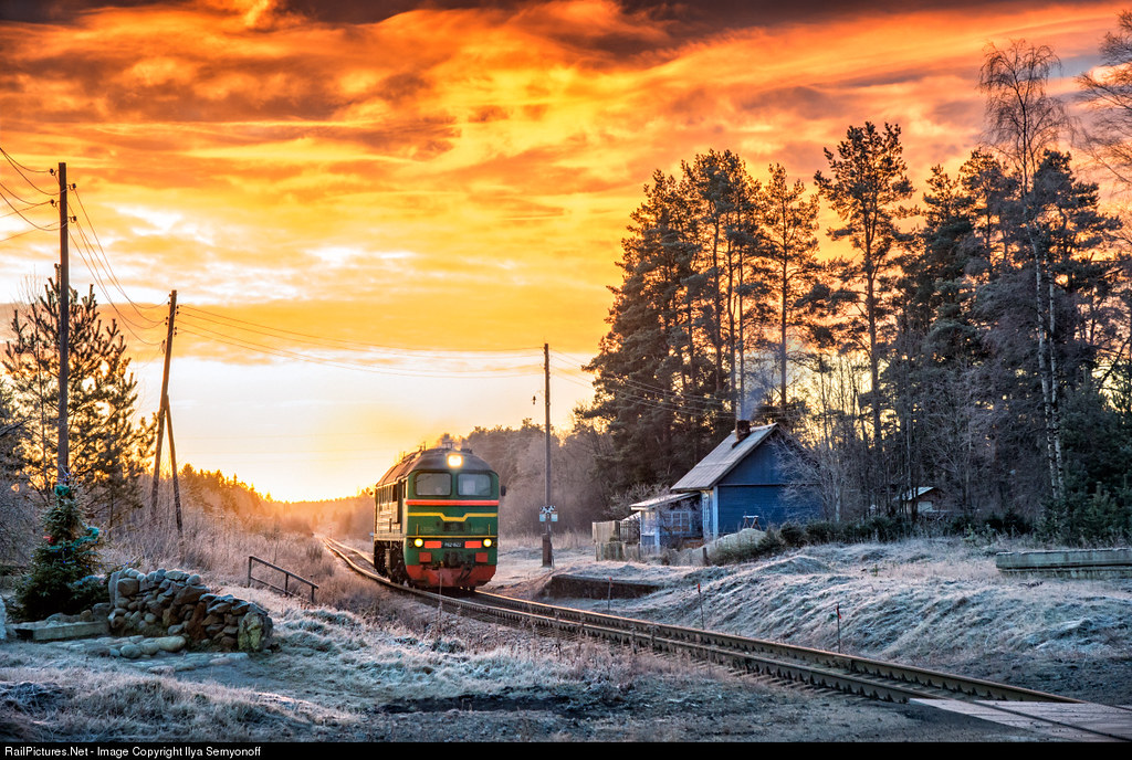 Russian Railways, Hiitola, Karelia, December 28, 2015. M62 Diesel locomotive #1622  goes through the train stop 168 km at the sunrise... Railroad line Losevo-Hiitola