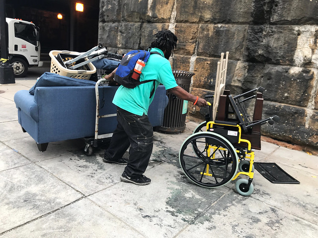 Photo of a man in a cyan shirt pushing a yellow wheelchair and pulling a flat moving cart with a blue couch and other belongings on top of it.